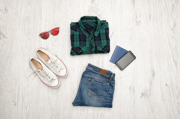 Blaugrünes kariertes hemd, brille, turnschuhe, jeans, telefon und reisepass