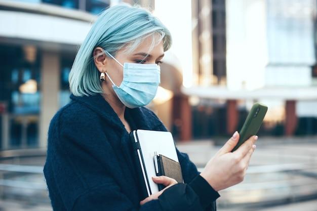 Blauhaarige frau, die draußen mit einem computer und telefon aufwirft, während sie eine spezielle antivirenmaske trägt