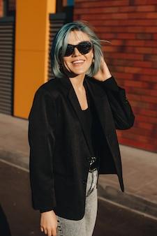 Blauhaarige geschäftsfrau, die draußen in der straße posiert, die brillen nahe einer backsteinmauer trägt und lächelt