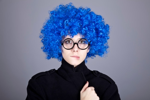 Blauhaariges mädchen der lustigen mode in den gläsern und im schwarzen mantel.