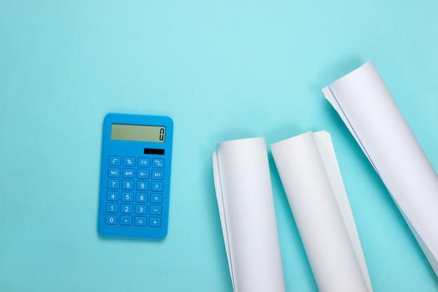Blaupausenrollen und taschenrechner auf blau. berechnung der kosten für den bau eines hauses. flach liegen