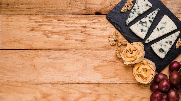 Blauschimmelkäse auf schieferstein; nussbaum; trauben und rohe teigwaren über tisch mit platz für text