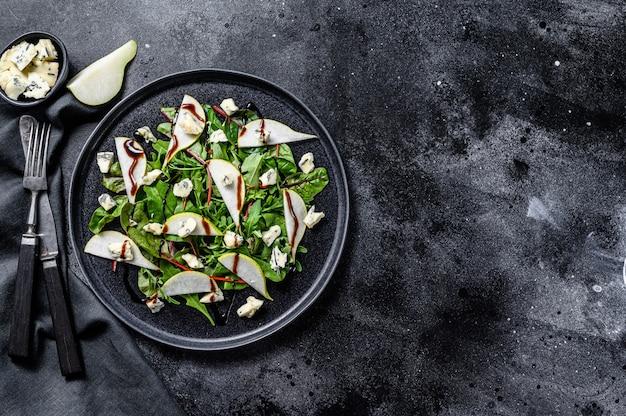 Blauschimmelkäsesalat mit birnen, nüssen, mangold und rucola. schwarzer hintergrund. draufsicht. speicherplatz kopieren