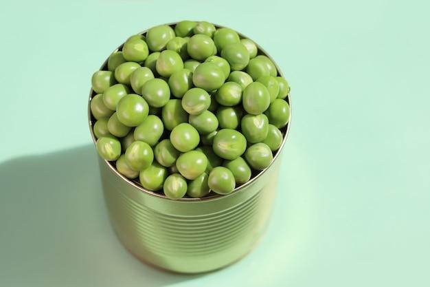 Blechdose, komplett gefüllt mit frischen grünen erbsen mit überschuss, nahaufnahme