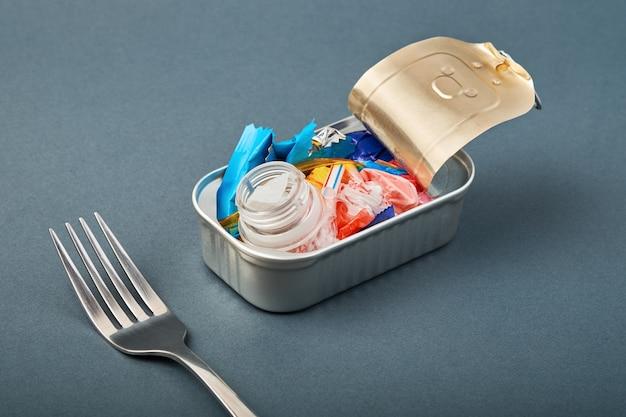 Blechdose und gabel öffnen. plastikmüll statt fisch im inneren. ozeanplastikverschmutzungskonzept