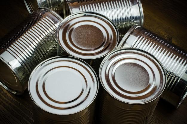 Blechdosen für lebensmittel auf hölzernem hintergrund.
