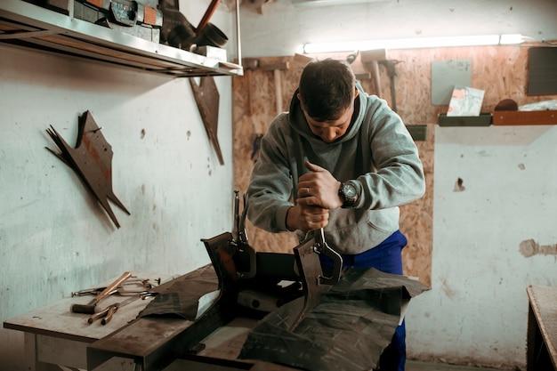 Blechschmied schmied verwendet hammer in seiner werkstatt.