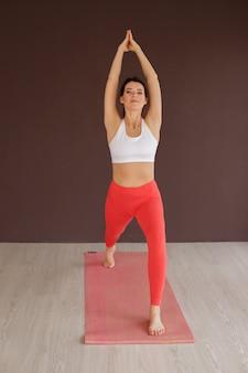 Bleib fit und sei gesund. schöne junge frau in sportbekleidung, die yoga tut.