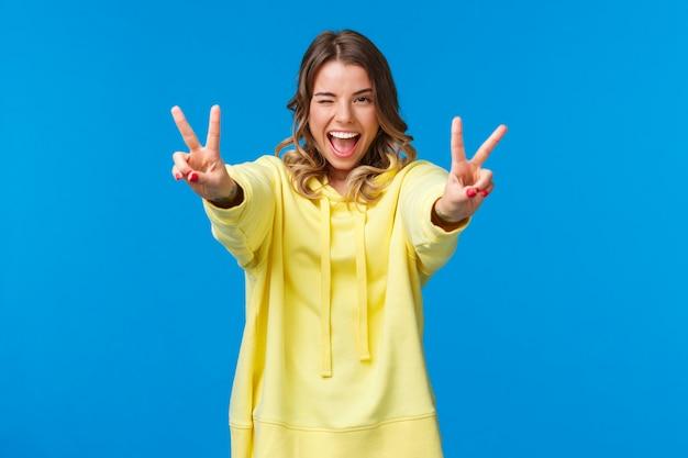 Bleib positiv. kawaii freudige, freundlich aussehende lächelnde blonde frau in gelbem kapuzenpulli, streckt die hände mit friedensgesten nach vorne, zeigt zunge und grinst, fühlt sich aufgeregt und optimistisch