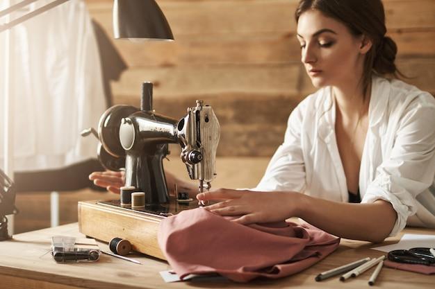 Bleib ruhig und nähe mit leidenschaft. innenaufnahme der frau, die mit stoff auf nähmaschine arbeitet und versucht, sich in werkstatt zu konzentrieren. junge kreative designerin, die neues kleidungsstück für ihre freundin macht