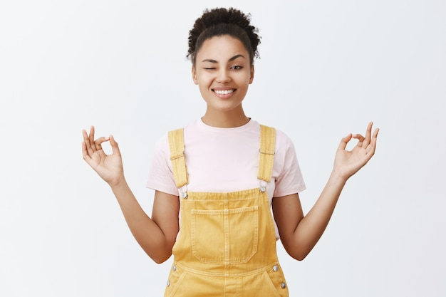 Bleib ruhig und stressfrei mit meditation. freudige und verspielte stilvolle moderne afroamerikanerin in gelben overalls, die mit einem auge späht und breit lächelt und hände in zen-pose hält