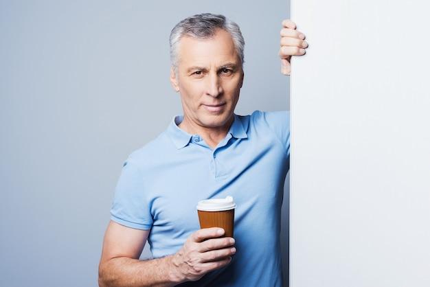 Bleib ruhig und trink kaffee. hübscher älterer mann, der eine tasse kaffee hält und sich an den kopierraum lehnt, während er vor grauem hintergrund steht