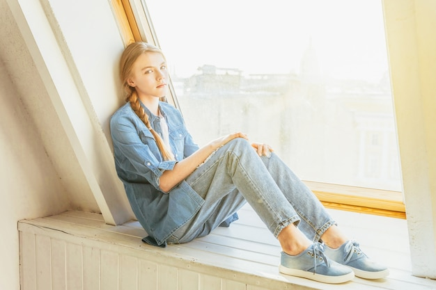 Bleib zu hause bleib sicher. junges süßes junges mädchen in jeans, jeansjacke und weißem t-shirt, das auf fensterbank im hellen hellen wohnzimmer zu hause drinnen sitzt und denkt. soziale distanz jomo konzept.