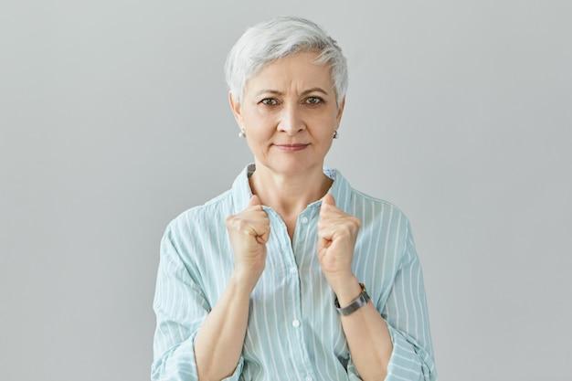 Bleibe stark. selbstbestimmte großmutter in stilvollem hemd, die die fäuste geballt hält und ihr enkelkind ermutigt. ältere gewinnerin ballt die fäuste und drückt freude und aufregung aus
