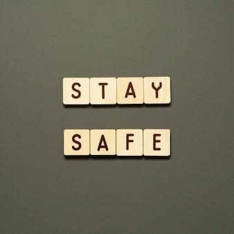 Bleiben sie sicher - wörter aus holzklötzen mit buchstaben. draufsicht