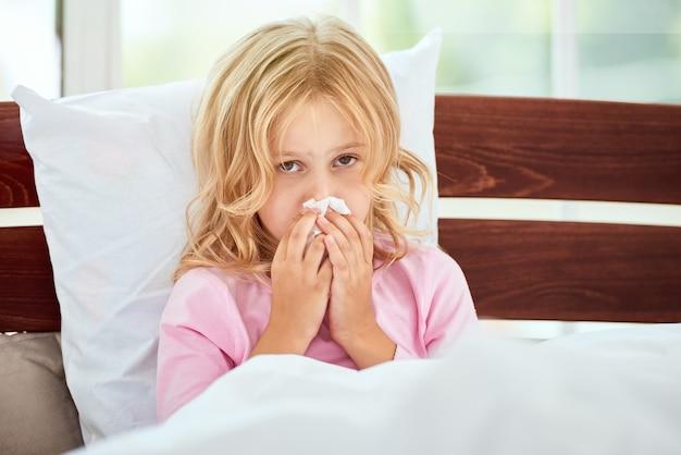 Bleiben sie zu hause porträt eines kleinen mädchens mit laufender nase, das an erkältung oder grippe leidet, während
