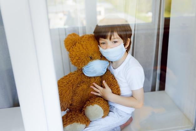 Bleiben sie zu hause quarantäne coronavirus pandemie prävention. trauriges kind sowohl in medizinischen schutzmasken in der nähe von fenstern als auch aus dem fenster