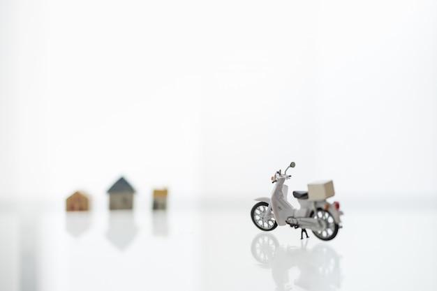 Bleiben sie zu hause, shelter in place mit lieferung und online-shopping-konzept. nahaufnahme von scotter / motorrad mit behälterbox und minihaus als hintergrund.