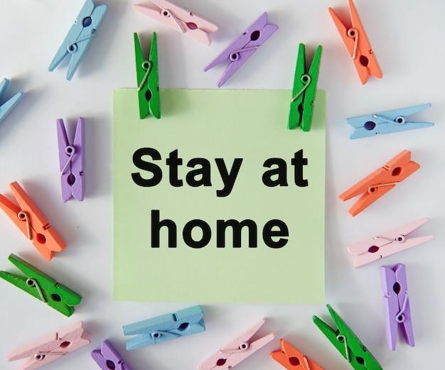 Bleiben sie zu hause - text auf einem notizblatt und mehrfarbige stecknadeln