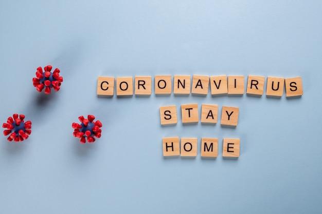 Bleiben sie zu hause und bleiben sie sicher. das konzept besteht aus holzbuchstaben und modellen des covid-19-virus