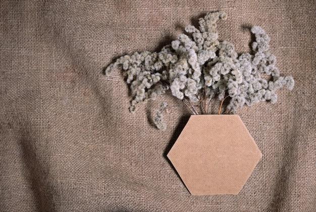 Bleibende verblasste nachhaltige blumen mit sechseckigem rahmen oder vase auf natürlichem leinwandleinwandhintergrund. zusammensetzung der getrockneten blumen für valentinstag, hochzeit oder frauentag in der natürlichen erdfarbenen farbe.