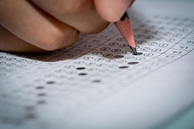 Bleistift an hand, der zum schreiben der antwort des fragentests auf mehrfach auserlesenem papier hält