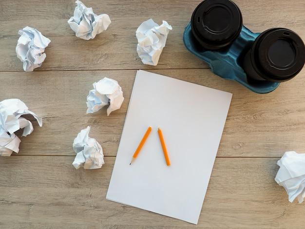 Bleistift auf klarem weißem papier mit krümelpapierball
