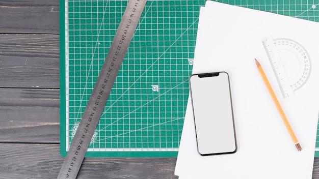 Bleistift in der nähe von papieren, smartphone, lineal und winkelmesser