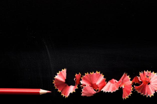 Bleistift mit schnitzeln auf schwarzem schreibtisch