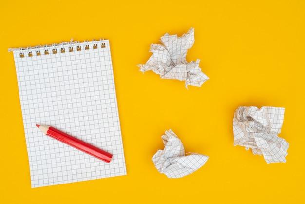 Bleistift, notizbuch und zerknittertes papier.