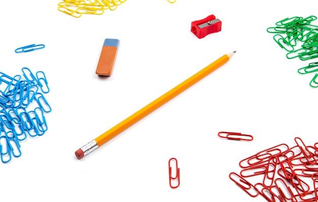 Bleistift, radiergummi, spitzer, büroklammern liegen in verschiedenen winkeln des blattes auf einem weißen hintergrund. heldenbild und textfreiraum.