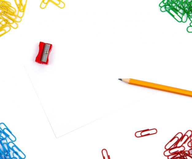 Bleistift, spitzer, büroklammern liegen in verschiedenen winkeln des blattes auf einem weißen hintergrund. heldenbild und textfreiraum.
