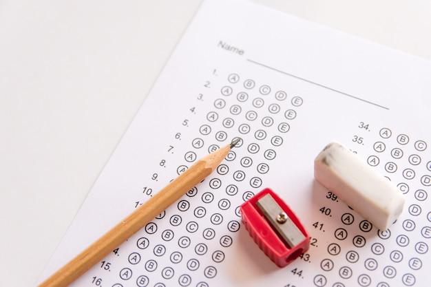 Bleistift, spitzer und radiergummi auf antwortblättern oder standardisiertes testformular mit antworten bubbl