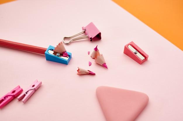 Bleistift und anspitzer auf rosa papierblatt, orange hintergrund. büromaterial, schul- oder bildungszubehör, schreib- und zeichenwerkzeuge