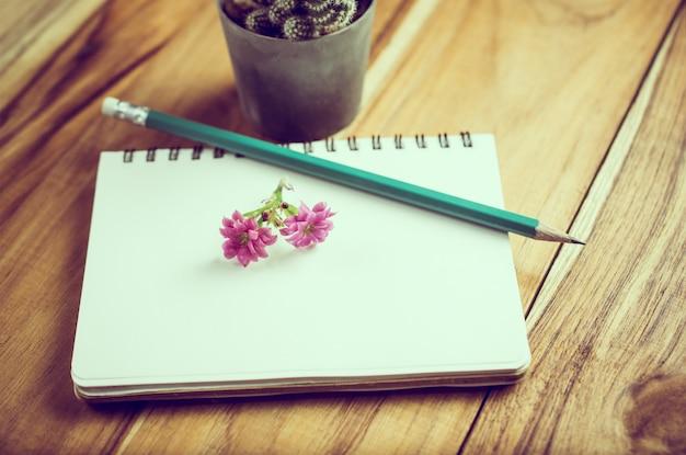 Bleistift und blume auf notizbuchpapierbildungskonzepthintergrund.