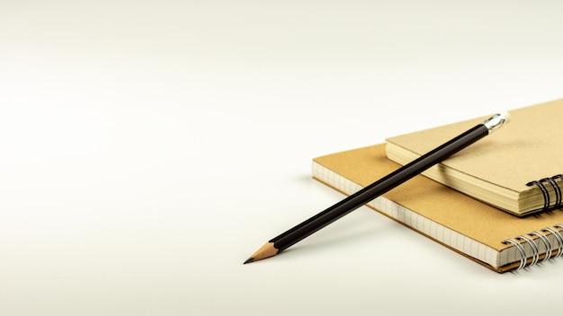 Bleistift und braunes tagebuchbuch auf weißem schreibtischhintergrund.