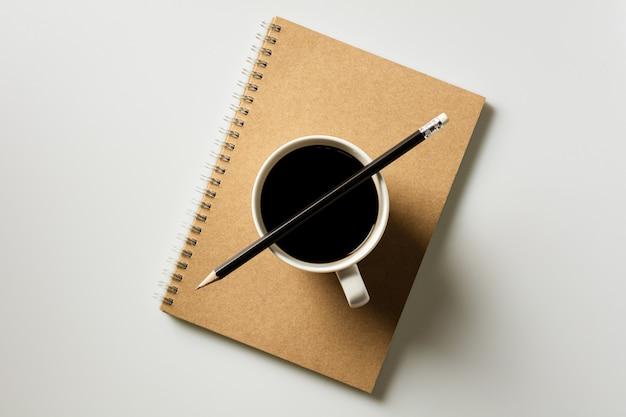 Bleistift und eine kaffeetasse auf tagebuchbuch am schreibtisch. - konzept von zu hause aus arbeiten.