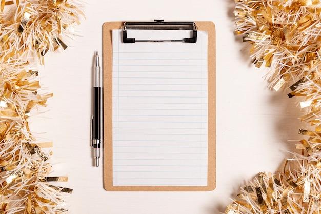Bleistift und klemmbrett mit weihnachtsdekorationsrahmen
