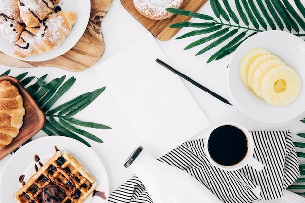 Bleistift und leeres papier in der mitte des frühstücks auf weißem schreibtisch