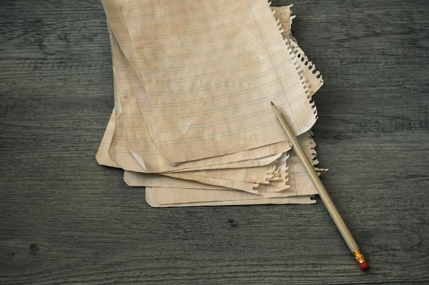 Bleistift und liniertes papier auf hölzerner tischplatte