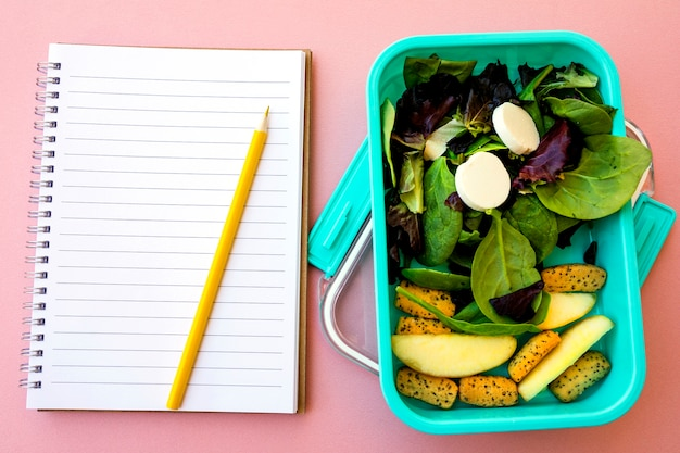 Bleistift und notizbuch in der nähe von salat