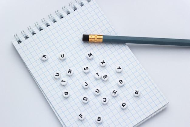 Bleistift und notizbuch mit buchstaben auf einem weißen hintergrund, konzept des schreibens eines briefes
