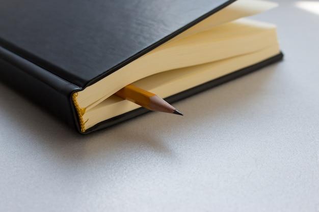Bleistift und notizbuch oder heft oder organizer. schulstunde, bürotreffen, briefe schreiben.