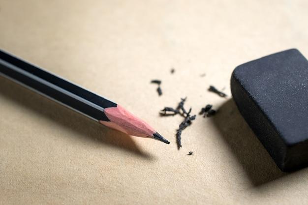 Bleistift und radiergummi auf braunem papierfehler, risiko, löschen.