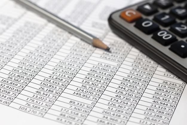 Bleistift und taschenrechner auf schreibtischtabelle mit finanzkonto dokumentieren bericht.