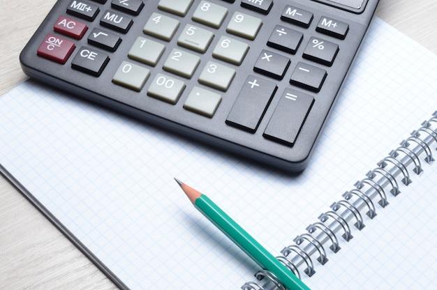 Bleistift und taschenrechner liegen auf einem offenen notizbuch. nahaufnahme.