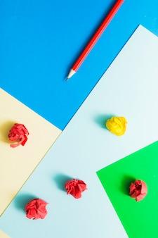 Bleistift und zerknittertes papier auf buntem kartenpapier