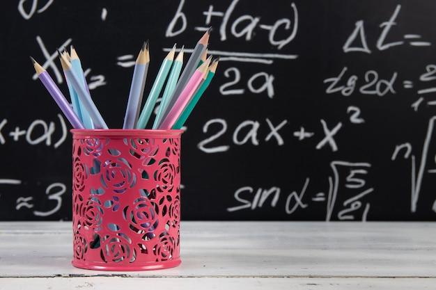 Bleistifte auf tafelhintergrund mit mathematischen formeln