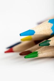 Bleistifte, die zum zeichnen gefärbt sind, sehen näher auf weißem schreibtisch