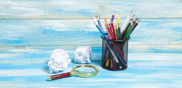 Bleistifte in einem ständer, eine lupe und zerknüllte papiere auf dem tisch. konzeptidee zum zeichnen
